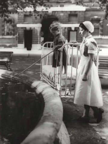 oy in dressing gown and coat, fishing in the fountain Description Supervised by a nurse. Beds, a shelter and parked cars in the background.