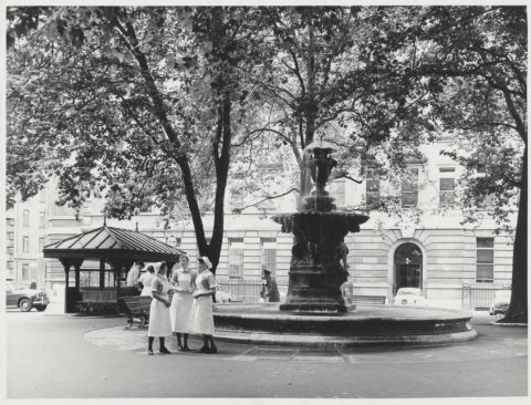"""""""The Square in summer, with nurses talking beside the fountain. Group of uniformed nurses, a uniformed porter and a patient. One of the shelters is visible and there are a few cars parked in the Square."""""""