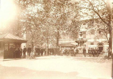 """""""Doctors and students congregating in the Square. Several dozen men are conversing in the Square; some are seated on the rim of the Fountain, at right. The North and East Wings are visible behind them, and the trees are in full leaf. A duplicate of part of this photograph (SBHX8/169.1) is dated June 1906 and inscribed """"""""1 o'clock"""""""", indicating the time when junior doctors and students assembled to await the start of the ward rounds."""""""