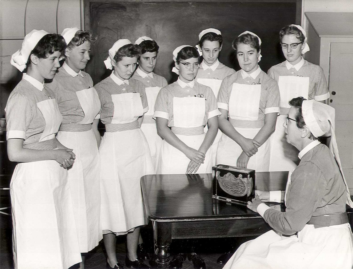 """SBHX8/567 """"Winifred Hector teaching student nurses in uniform, c.1960. Hector seated at right with gastric specimen on table. Eight second year student nurses [indicated by their belts] standing, from the Oct 1958 set."""" 1960 Nursing Mirror"""
